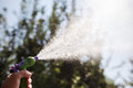 Hand with hose sprinkle watering plants in the garden Royalty Free Stock Images
