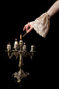 Hand igniting candles in old fashioned lace sleeve an antique candlestick Stock Photography