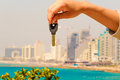 Hand with a key in the background of the sea with buildings and Royalty Free Stock Photo