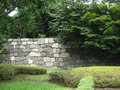 Hand laid stone wall with trees and lawn of rocks that form a fort around a castle in japan Royalty Free Stock Image