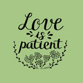 Hand lettering Love is patient, made near flowers. Royalty Free Stock Photo