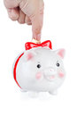 Hand lowers a coin in a pig a-coin box Royalty Free Stock Image