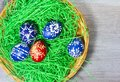 Hand made easter egg in green grass and basket on rustick wooden Royalty Free Stock Photo