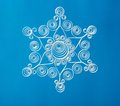 Hand made paper christmas snowflake нand on blue background Stock Image