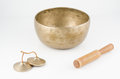 Hand made singing bowl with ringing stick and meditation bells on a white background Royalty Free Stock Photography