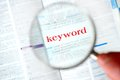 Hand magnifying keyword from book Royalty Free Stock Images