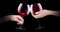 Hand making toast with wine glass of red splashing on black background Royalty Free Stock Image