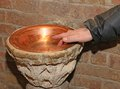 Hand of man and an ancient stoup inside the church holy water font in a copper vase Royalty Free Stock Photos