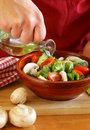 Hand man chef cooking vegetable salad on wooden table Royalty Free Stock Images