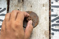 Hand man install rusty nut and bolt on wood