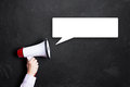 Hand with a megaphone in front of a blackboard Royalty Free Stock Photo