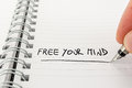 Hand met pen writing free your mind in notitieboekje Stock Fotografie