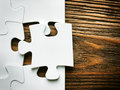 Hand with missing jigsaw puzzle piece business concept image for completing the final puzzle piece wooden background Royalty Free Stock Photo