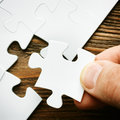Hand with missing jigsaw puzzle piece business concept image for completing the final puzzle piece wooden background Stock Photography