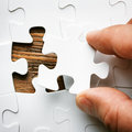 Hand with missing jigsaw puzzle piece business concept image for completing the final puzzle piece wooden background Stock Photos