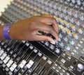 Hand on a mixing desk close up of black girls turning knob sound Royalty Free Stock Images