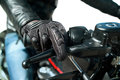 Hand of motorcyclist closeup the in protective glove on a throttle control on white Stock Image