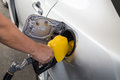 Hand with nozzle fueling unleaded gasoline into car at station Stock Photos