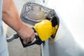Hand with nozzle fueling unleaded gasoline into car at station Stock Photography