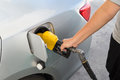 Hand with nozzle fueling unleaded gasoline into car at station Royalty Free Stock Photography