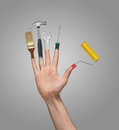 Hand with an open palm and tools instead of fingers on a gray background. Brush, hammer, wrench, screwdriver, paint roll Royalty Free Stock Photo