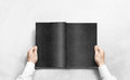 Hand opening black journal with blank pages mockup. Royalty Free Stock Photo