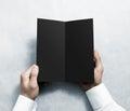 Hand opening blank black flyer brochure booklet mockup. Leaflet presentation. Royalty Free Stock Photo