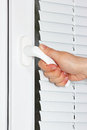 Hand opens the white plastic window with shutters Stock Image