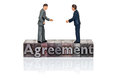 Agreement word in letterpress with miniature businessmen Royalty Free Stock Photo
