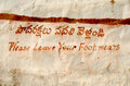 Hand painted sign in english and telugu asking visitors to an historic hindu temple to remove their shoes golcanda fort hyderabad Stock Photos