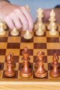 Hand with pawn makes first move on chess Board Royalty Free Stock Photo