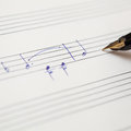 Hand with pen and music sheet pointing to book handwritten notes Royalty Free Stock Photo