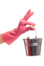 Hand in a pink glove holding silver pail domestic isolated over white background Stock Photography