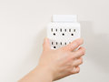Hand plugging in multiple electrical unit into wall outlet photo of female socket units Royalty Free Stock Photos