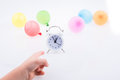 Hand pointing an alarm clock  with baloons around Royalty Free Stock Photo