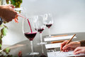 Hand pouring red wine at wine tasting. Royalty Free Stock Photo