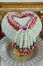 Hand pouring in thai wedding flower heart shaped garland put on silver tray Royalty Free Stock Image
