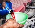 Hand pouring transmission fluid through funnel as for the good car maintenance Stock Photography