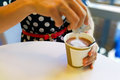 Hand pouring unhealthy non dairy creamer from sachet into coffee Royalty Free Stock Photo