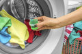 Hand pours liquid powder into the washing machine. Royalty Free Stock Photo