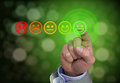 Hand pressing green smiley button of performance rating Royalty Free Stock Photo