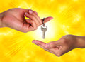 Hand property buying keys success a handing a set of silver to someone else with a yellow sun sky background Royalty Free Stock Images