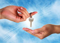 Hand property buying keys success a handing a silver key to someone else with a blue sky background Royalty Free Stock Photography