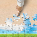 Hand pushing puzzles to assembly with beautiful landscape on wooden table Royalty Free Stock Photos