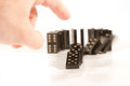 Hand pushing a row of dominoes human black shallow dof selective focus on the finger and domino piece in front the Royalty Free Stock Photos