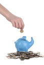 Hand puts a coin in a piggy bank the ruble into Stock Images