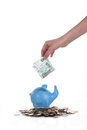 Hand puts the ruble into a piggy bank down thousand rubles in Stock Photo