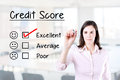 Hand putting check mark with red marker on excellent credit score evaluation form. Office background. Royalty Free Stock Photo