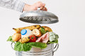 Hand putting lid on garbage can full of waste food puts Stock Photo