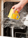 Hand putting a mug into a dishwasher yellow Royalty Free Stock Images